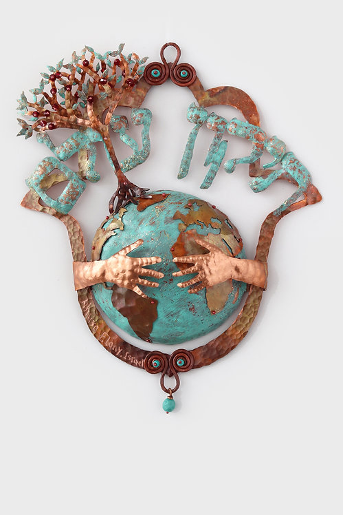 A picture of a hamsa made of copper in which appears the earth embraced by the hamsa at the top of the hamsa is written Tikun