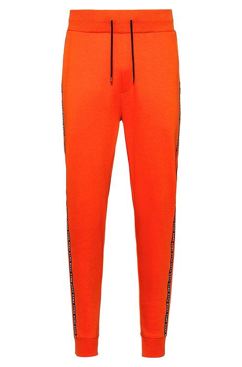 Pantalon HUGO en coton interlock resserré au bas des jambes, avec rubans logo sur les coutures latérales