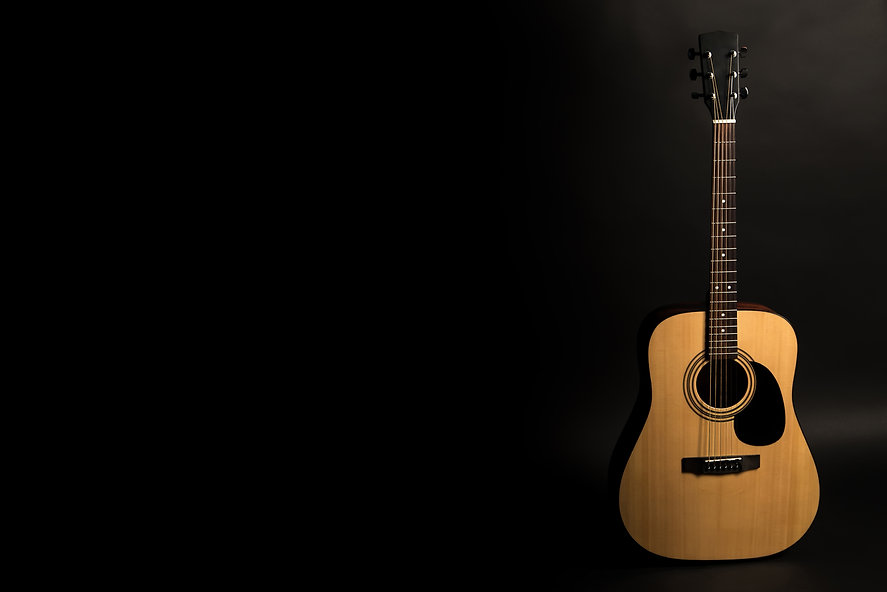 Acoustic guitar on a black background on
