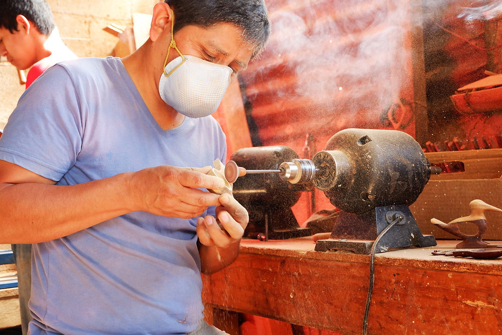 A man carving wood on a routing machine in his workshop in Guatemala