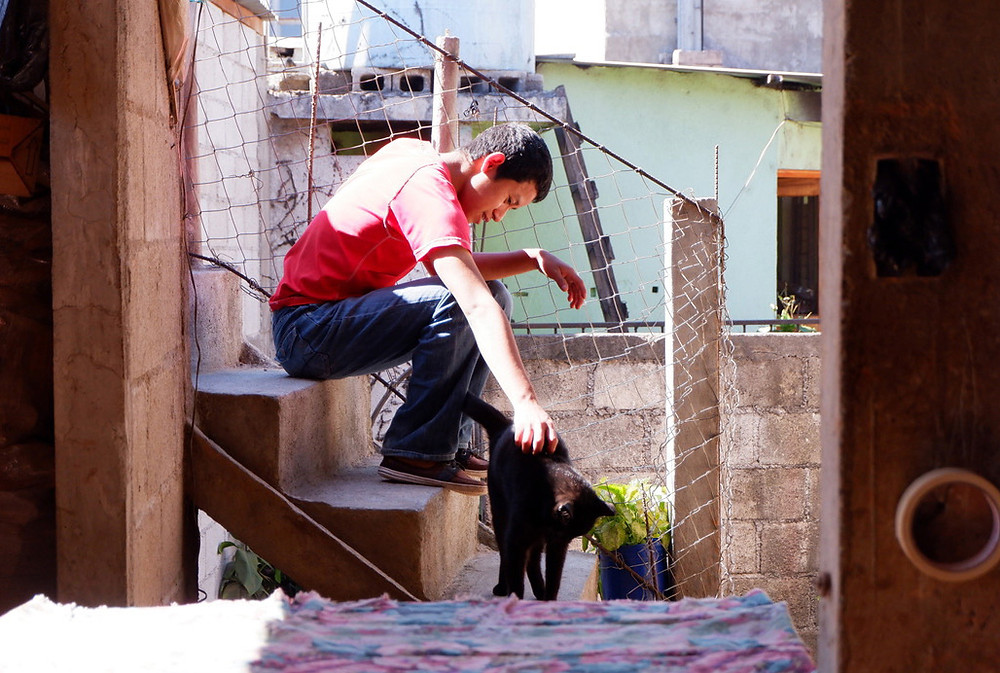 Boy with cat in Guatemalan house