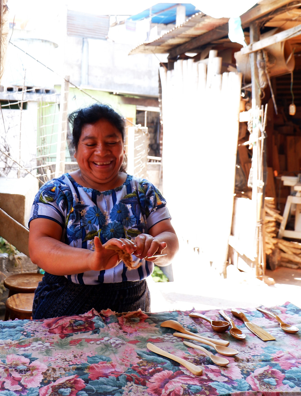 Lady in traditional Guatemalan Traje polishing wooden cutlery