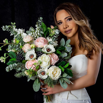 A woman with tan skin in a white dress holds a large, messy bouquet of anemone, white ranunculus, pink ranunculus, sage greenery, and other bouquet elements against a black background.