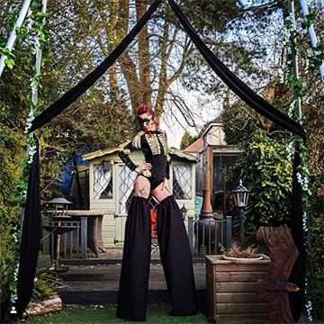A woman stands outdoors under a black ribbon arch whilst wearing a black leotard and black masquerade mask and she has black legwarmers on over tall stilts.