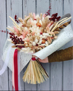 A light pink and tan bouquet being held against grey barnwood background.