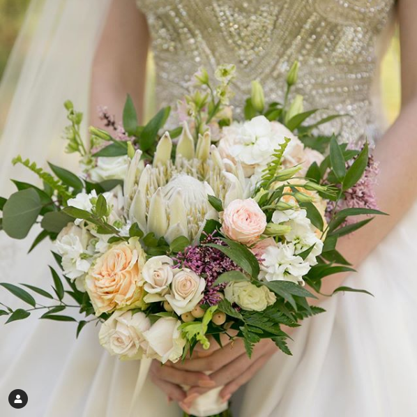 A bride holds a bouquet of greenery, purple, white, and light pink flowers in front of a beaded corset gown.