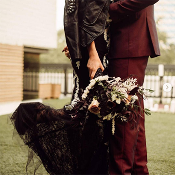A bride in a black dress holds her dark bouquet near her knees as she kisses her groom, who is wearing a maroon suit.