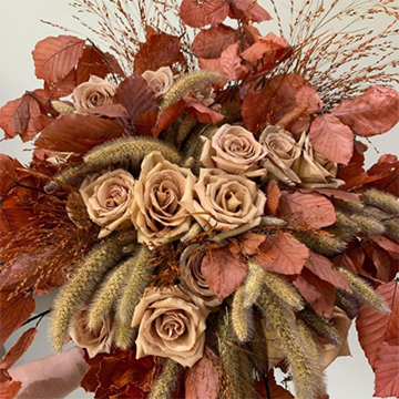 A bouquet with dried tan roses, lots of fluffy dried grasses, and red leaves as greenery is held in front of a white background.