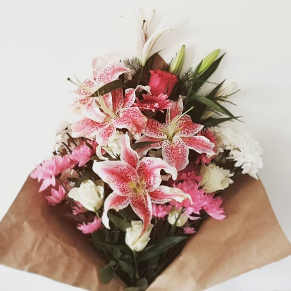A bouquet of pink lilies, roses, and various white flowers is wrapped in brown paper in front of a white background.