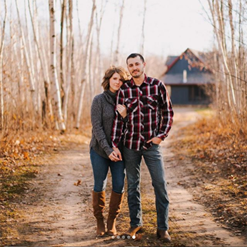 A man stands in red and black plaid and jeans while holding a brunette woman's hand and standing on a dirt path in a birch forest. There are fall leaves on the ground and a deep blue house far in the background.