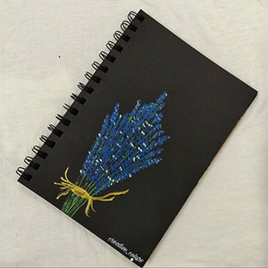 A black notebook lays on a white surface with a drawing of a bundle of purple lavender on the front.