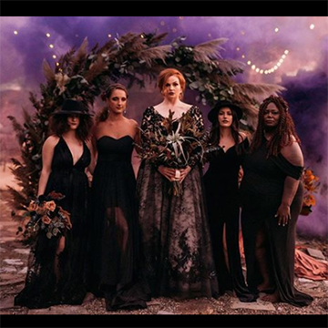 A bride and her bridesmaids stand in black dresses under an arch of flowers and grasses in front of a witchy, purple night sky background.