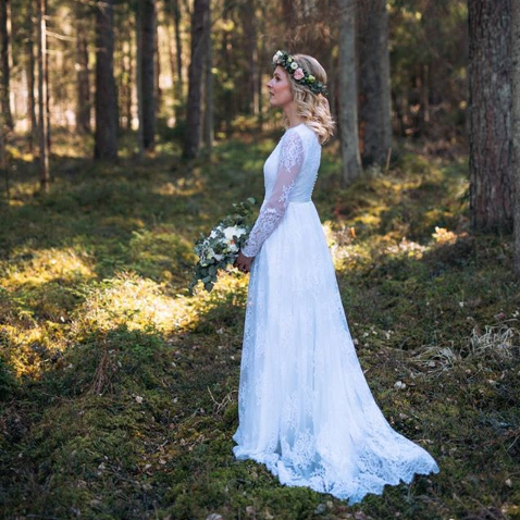 A bride with a flower crown stands in the middle of a mossy glade in the woods, holding her bouquet in front of her dress. We are looking at her from the side.