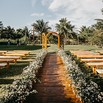 A wooden arch sits at the end of an outdoor aisle, which is lined with bushes of little white flowers.