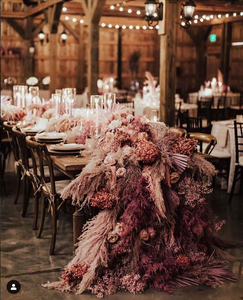 A large table centerpiece of purple and red roses, seeds, and other dried plants.