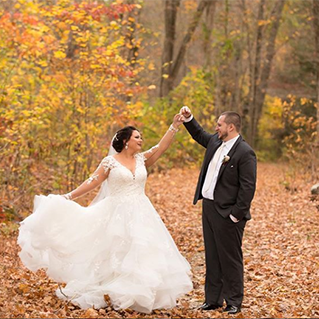 A bride and groom dance in the orange and yellow fall leaves in front of a forest background.