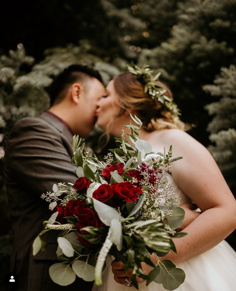 A young bride kisses her groom's cheek in the background while holding a bouquet of red roses and greenery in the foreground.
