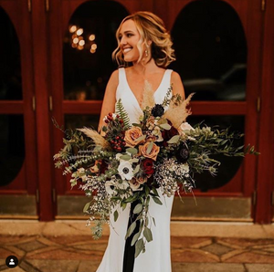 A blonde bride holds a large bouquet of wild ferns, greenery, roses, and anemones.