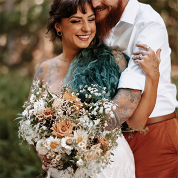 A groom in brown-orange pants with a brown-orange beard cuddles his bride with black and teal hair while they hold her large, rustic bouquet in front of her.