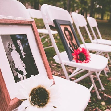 A line of white chairs sits on grass with different framed portraits on each seat. One has a white sunflower and the other has a pink sunflower also sitting on the seats.