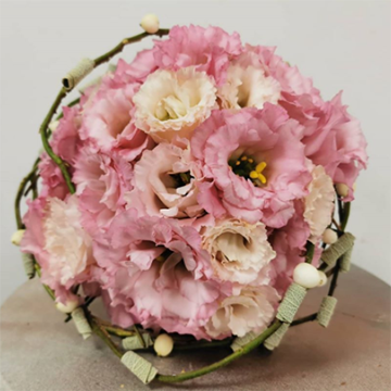 A tight round bouquet of pink and light peach lisianthus flowers sits on a wooden table. We view the bouquet from its top. It has green vines or twigs around its base as decoration.