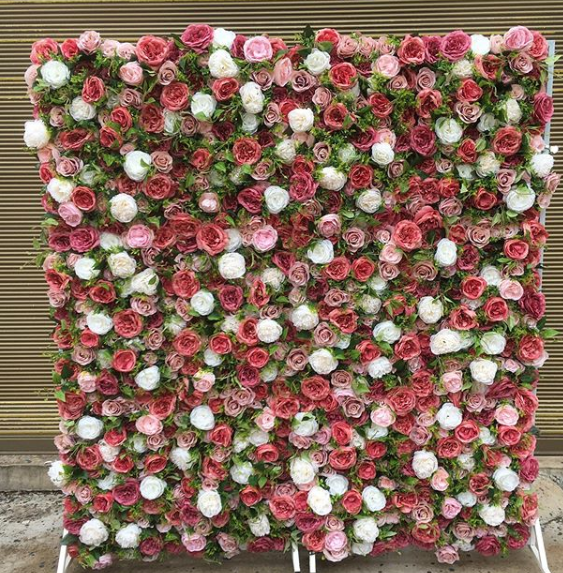 A wall of pink, red, and white roses and ranunculus.