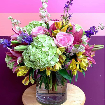 A colorful bouquet with pink roses, lilies, tulips, and white and blue delphinium/larkspur sits in front of a purple background.