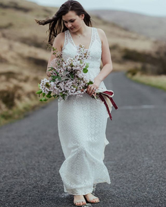 A beautiful bride walking down a blacktop road with a simple dress and a large bouquet featuring cherry blossoms and greenery.
