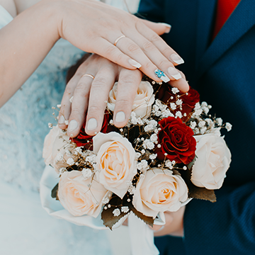 A couple holds their red and white rose bouquet with baby's breath in between the blooms and the bride holds her hand on top of the bouquet to display her ring.