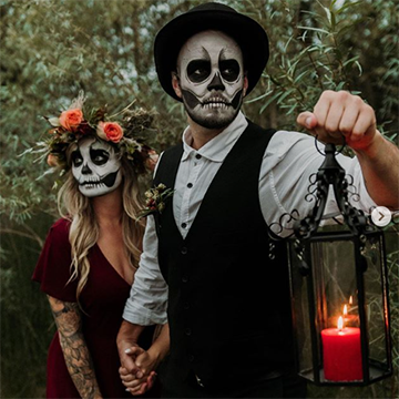 A man in skeleton face paint holds up a black lantern with a red candle in front of him. He is also holding a girl's hand behind him as they appear to travel through the forest together. The woman has matching skull face paint on and a red dress. She has flowing blonde hair with a messy flower crown of greenery and pink ranunculus in it.
