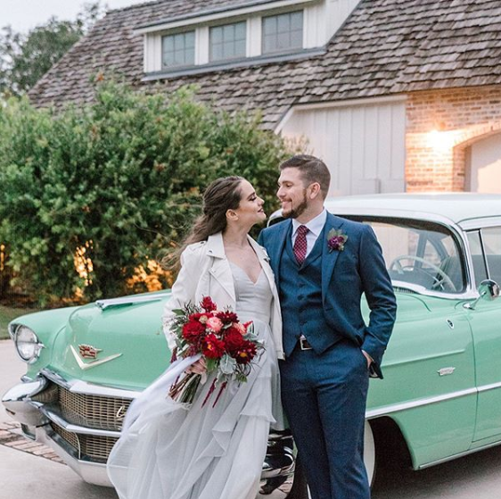 A bride holds a smal round bouquet of greenery and red flowers while hugging her groom in front of a vintage mint green car.