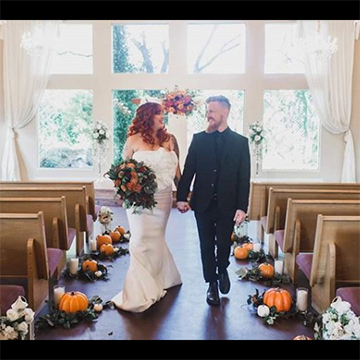 A bride and groom hold hands while walking down an aisle lined with orange pumpkins sitting in greenery. A bright, bay window with white curtains sits in the background.