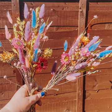 A hand with blue finger nails holds two small sprigs of dried grasses and wheat and small flowers in bright blues, pinks, and purples against a wood background.