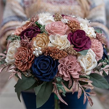 Someone in a white-brown sweater holds out a bouquet of wooden flowers in shades of blue, burgundy, white, light pink, and gold with rose gold and sage greenery.