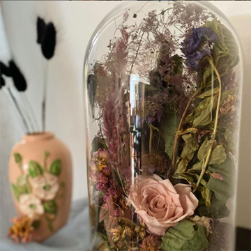 A bell jar holds a collection of brown and green dried florals with one pink rose in the center.