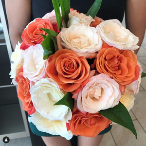 A round bouquet with salmon-colored, white, and light pink roses  and green leaves poking out.
