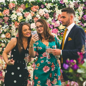 Three friends in front of a wall of peach, purple, and white flowers taking a selfie.