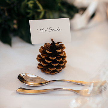 "A pine cone sits on a white table with a spoon and fork in front of it and a beautiful name card with calligraphy on it sitting in its top that says, ""The Bride""."