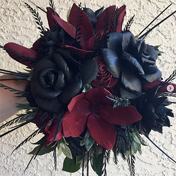 A bouquet of wooden flowers (black roses, burgundy flowers, and black ferns, among others) is held in front of a textured, white wall.