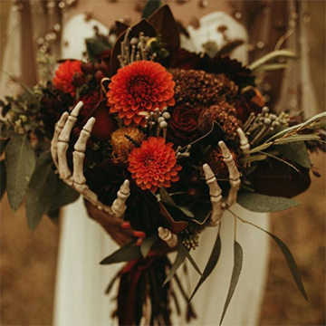 A bride holds her autumn-themed bouquet of dried greens  and various orange to red flowers and fresh dahlias in a dark salmon color. The underside of the bouquet is decorated with skeleton hands that appear to hold the bouquet.