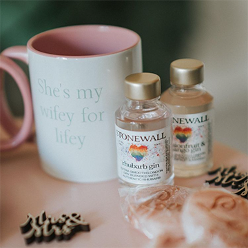 """A white and pink coffee mug says """"She's my wifey for lifey"""" and sits with some small sample gin bottles, small pink favor bags, and small wooden decorations that say """"Mrs. & Mrs."""" in brush font."""