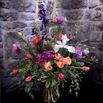 A messy bouquet of pink tulips, purple garden roses, and dark blue delphinium/larkspur sits in a vase in front of a stone wall.