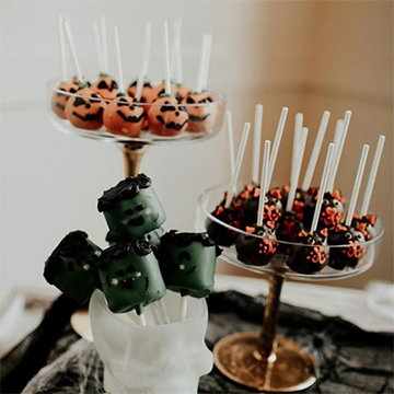 A tray of marshmallows decorated to look like Frankenstein heads, a tray of black cat-decorated cake pops, and a tray of cake poips decorated to look like jack-o-lanterns sit together on dishes of varying heights.