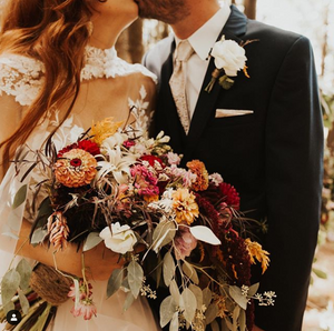 A bride holds her bouquet of messy greens and flowers with large blooms as she kisses her groom.
