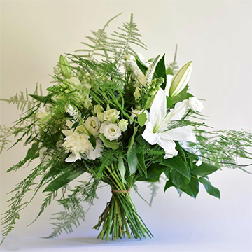 A bouquet stands on its own stems with one large, white lily, a lot of fern greenery, and some smaller white flowers all in front of a white background.