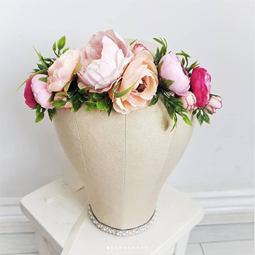 A flower crown sits on a head model with large peach, light pink, and dark pink ranunculus nested in greenery.