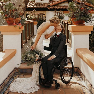A woman in a long, white lace dress holds a large, messy, dark green and pink roses bouquet while kissing a young man in a tuxedo who is sitting in a wheelchair in front of two pillars with beautiful desert foliage on top of them.