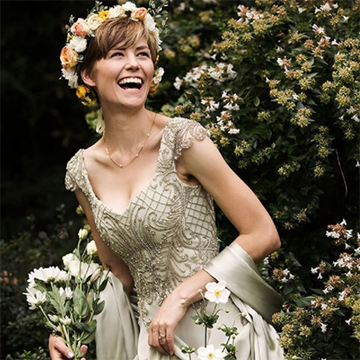 A bride in a beaded white dress smiles while wearing a peach, white, and sage green flower crown and holding a simple white bouquet.