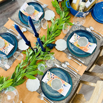 A place setting og blue faded dishes and orange napkins is seen from overhead. The place mats are grey burlap and there are tall, dark blue candles and bright greenery strewn across the middle of the table.