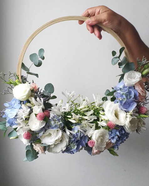 A hoop bouquet with a light wood handle and white, blue, and pink flowers.